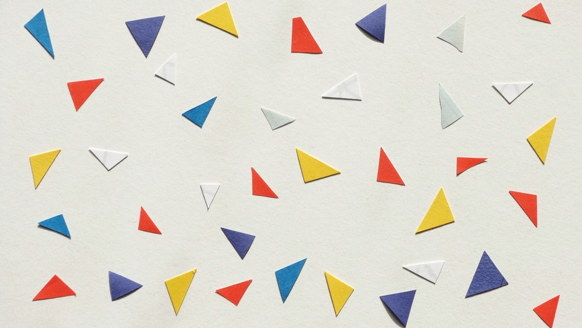 Purple, blue, yellow, red and white paper triangles on an all white background